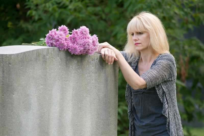 woman grieving at a grave in need of sympathy