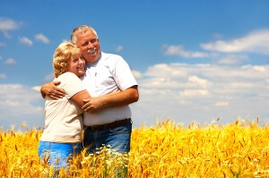Older couple holding each other in field