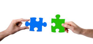 Two hands holding matching puzzle pieces