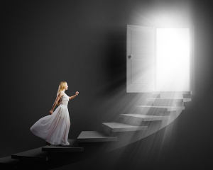 Woman climbing towards light