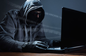 Hacker in mask stealing data from a computer