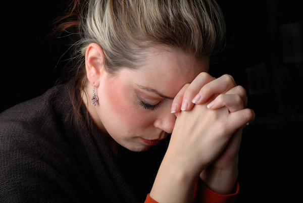 woman saying a prayer in brokenness