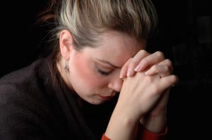 Woman praying in brokenness