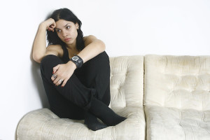 Young woman sitting on her sofa looking sad