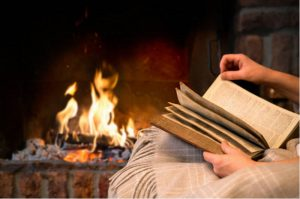 Reading by a fireplace with fire