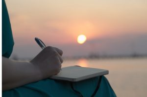 woman writing at sunset