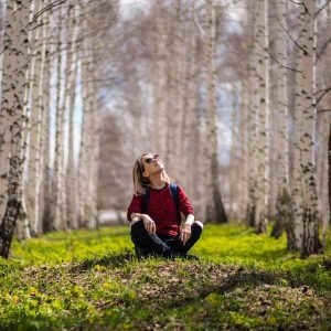 Woman outside in grove of birch trees