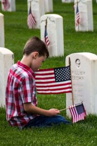 Memorial Day: gone but not forgotten - boy placing flag on grave at Arlington Cemetery